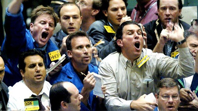 Buyers and sellers shout orders across a trading pit at the New York Mercantile Exchange early in the trading day, October 6, 2004 in New York. Oil prices neared $52 for U.S. crude, fueled by the impact of Hurricane Ivan on U.S. winter inventories. Oil has surged more than 55 percent since the start of the year, driven by the strongest demand growth in a generation and a thinning cushion of spare production capacity to cope with supply outages. REUTERS/Henny Ray Abrams  HRA - RTRCOT8